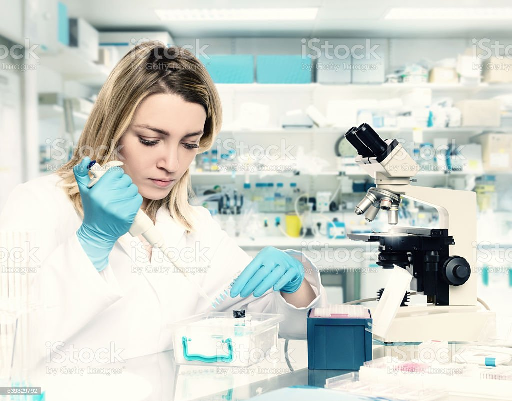 Young female tech or scientist works in research facility stock photo