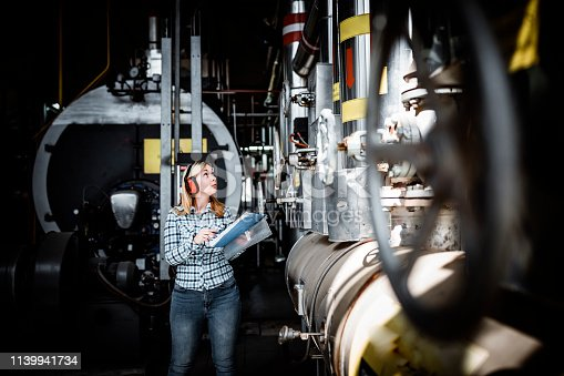 Attractive Woman Engineer is Inspecting the Boiling System at the Heating Plant. She is Standing in the Basement of the Power Station with Protective Headphones and is Doing Quality Control While Using her Notebook.
