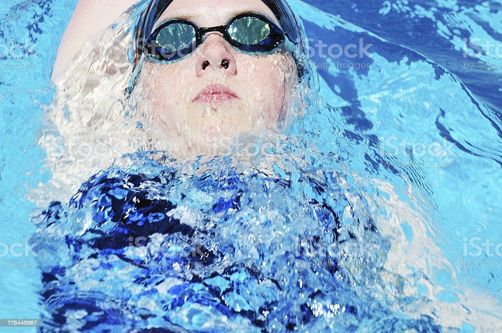 Young Female Teen Athlete Backstroke Swimmer Racing in Pool stock photo