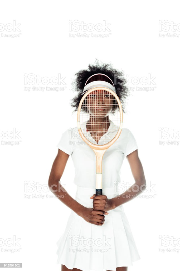 young female tennis player holding racket in front of face isolated on white stock photo