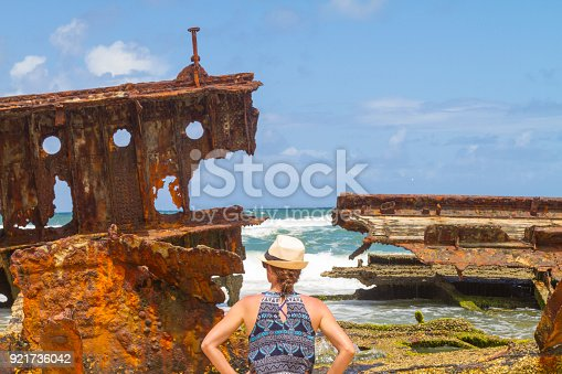 Young female traveler tourist taking a break in her vacations in front of Maheno shipwreck on Fraser Island, Queensland, Australia