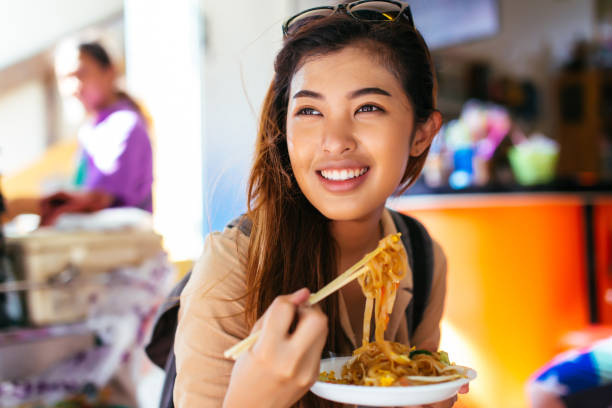 Junge Touristin isst Thai-Nudeln im Laden – Foto