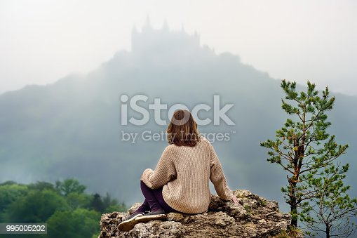 Young female tourist looking on famous Hohenzollern Castle in thick fog, Swabian Alps, Baden-Wurttemberg, Germany. Girl travel around Europe
