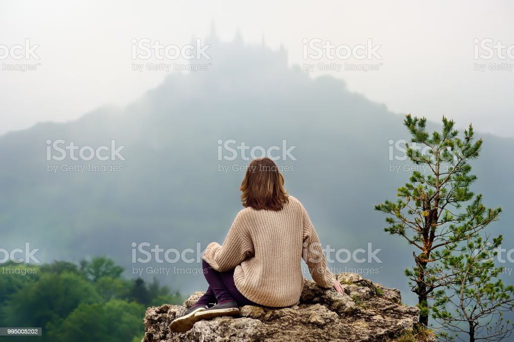 Young female tourist looking on famous Hohenzollern Castle in thick fog, Germany stock photo