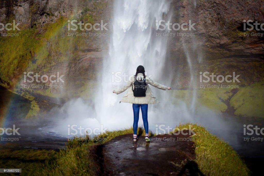 Joven turista en el fondo de una cascada - foto de stock