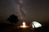 Camping night in mountains. Young pretty tourist girl sitting in entrance of lit from inside tent watching brightly burning bonfire under beautiful deep dark starry sky. Tourism and travel concept.