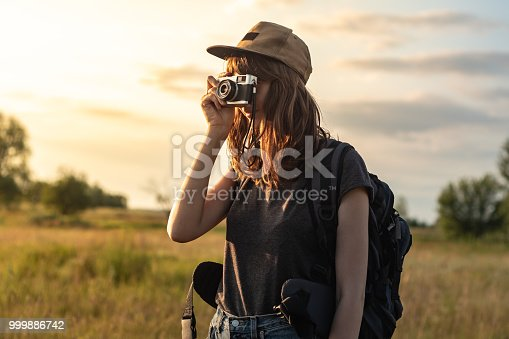 Woman with backpack stands at sunset and photographs beautiful rural area