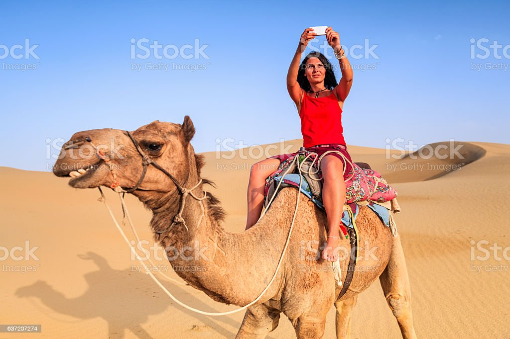 Young female tourist taking selfie on a camel, Rajasthan, India stock photo