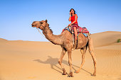 Young female tourist using mobile phone during riding camel, sand dunes.