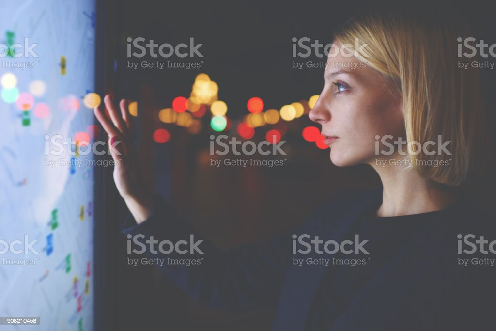 Young female tourist using smart city gadget to get direction in Barcelona central, female in night city standing front big digital screen with city map routes and locations shown on it,filtered image stock photo