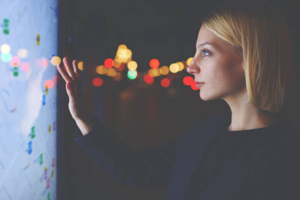 young female tourist using smart city gadget to get direction in barcelona central, female in night city standing front big digital screen with city map routes and locations shown on it,filtered image - interactivity stock photos and pictures