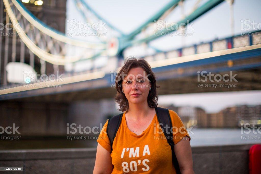 Young female tourist with tower bridge background, London, UK stock photo