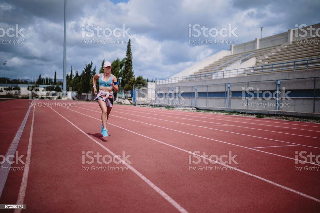 Young sporty woman listening to music and exercising by sprinting on...