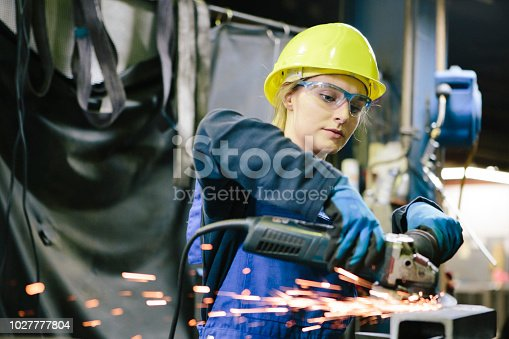 young female trainee welds steel with grinder in workshop, wearing work helmet and protective eyewear,