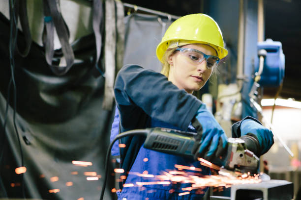 young female trainee welds steel with grinder in workshop stock photo