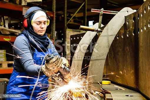 Young female trainee welds steel with grinder in workshop, flying sparks