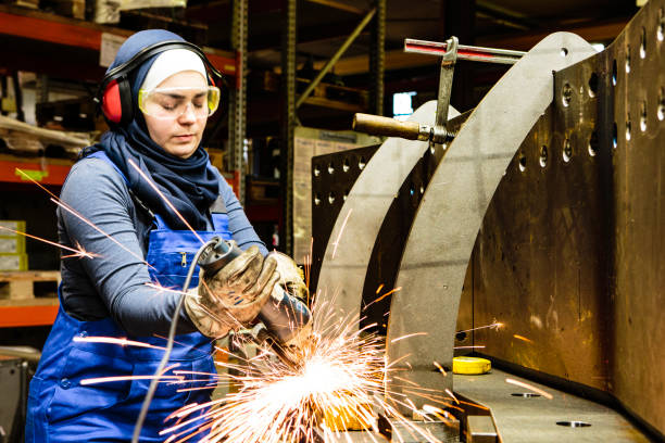 Young female trainee works with a grinder in a workshop, flying sparks stock photo