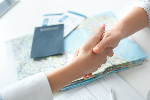 Young female travel agent consultant in tour agency with a customer handshake stock photo