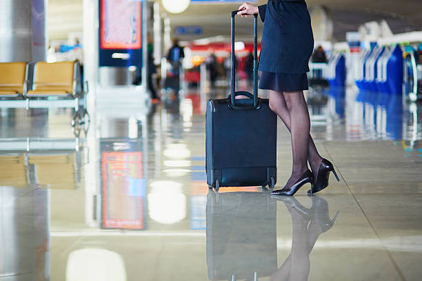 Young female traveler in international airport Beautiful female passenger or flight attendant in international airport with hand luggage cabin crew stock pictures, royalty-free photos & images