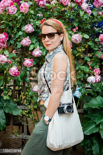 Young female traveler standing in front of wall of flowers