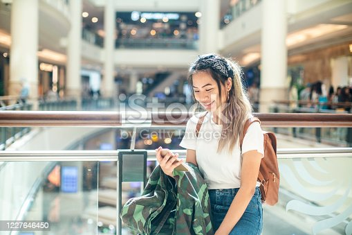 Young female traveler surfing on her mobile phone at the shopping mall