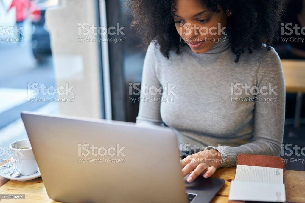 Young female trendy dressed student watching webinar about design and decoration during break in university library resting with cup of tea using wireless connection to 4G internet and laptop stock photo