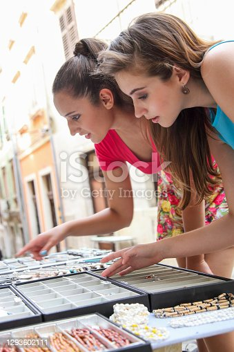 Two female friends choosing the best gift to buy on a trip. Tourists on a city street market.