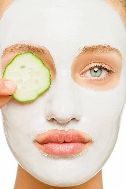 junge weibliche werden kosmetische behandlung - gurkenmaske stock-fotos und bilder