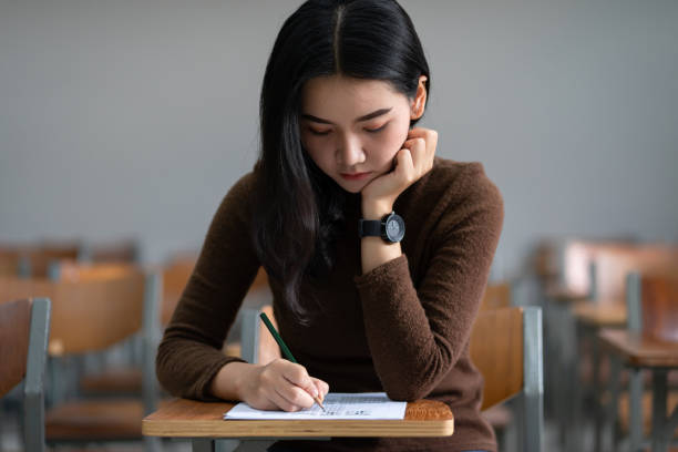 Young female university student concentrate doing  examination in classroom. Girl student writes the exercise of the examinations. University examination and education concept. stock photo