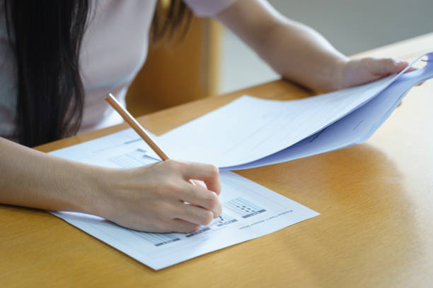 Young female university student concentrate doing language practice examination inside library with blur books shelve in background. Girl student writes the exercise of the examinations. stock photo