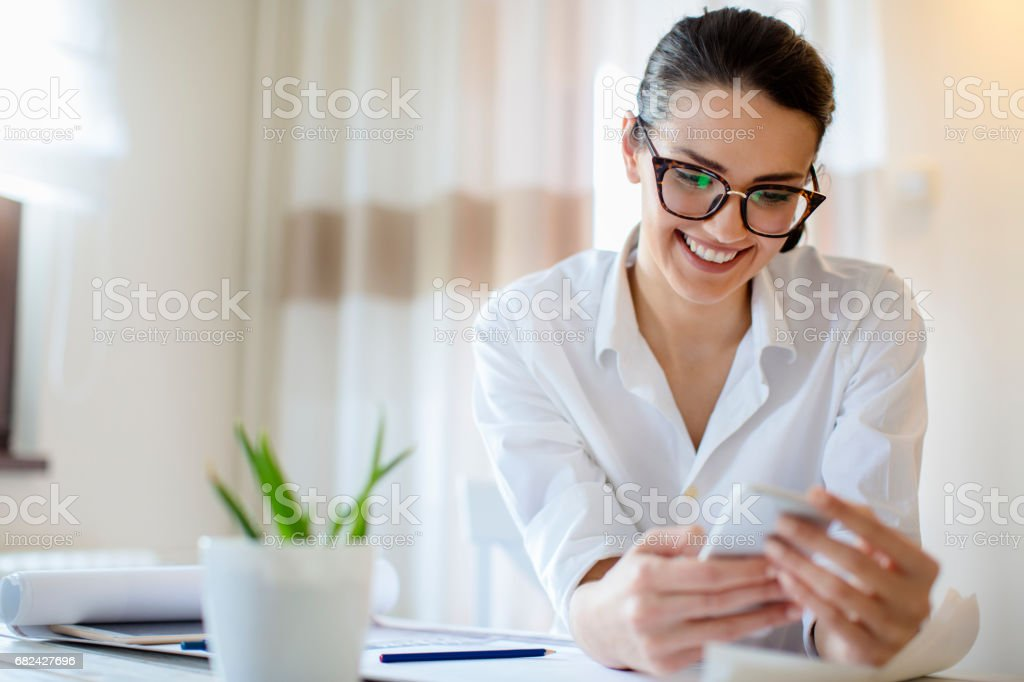 Young female using mobile phone at home royalty-free stock photo