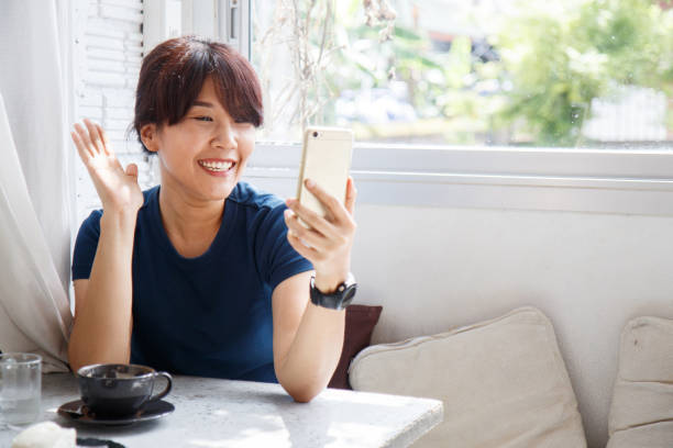 Young female video call talking with her friend on smartphone device.  Copy space. Young female talking with her friend on smartphone device.  Copy space. fan club stock pictures, royalty-free photos & images