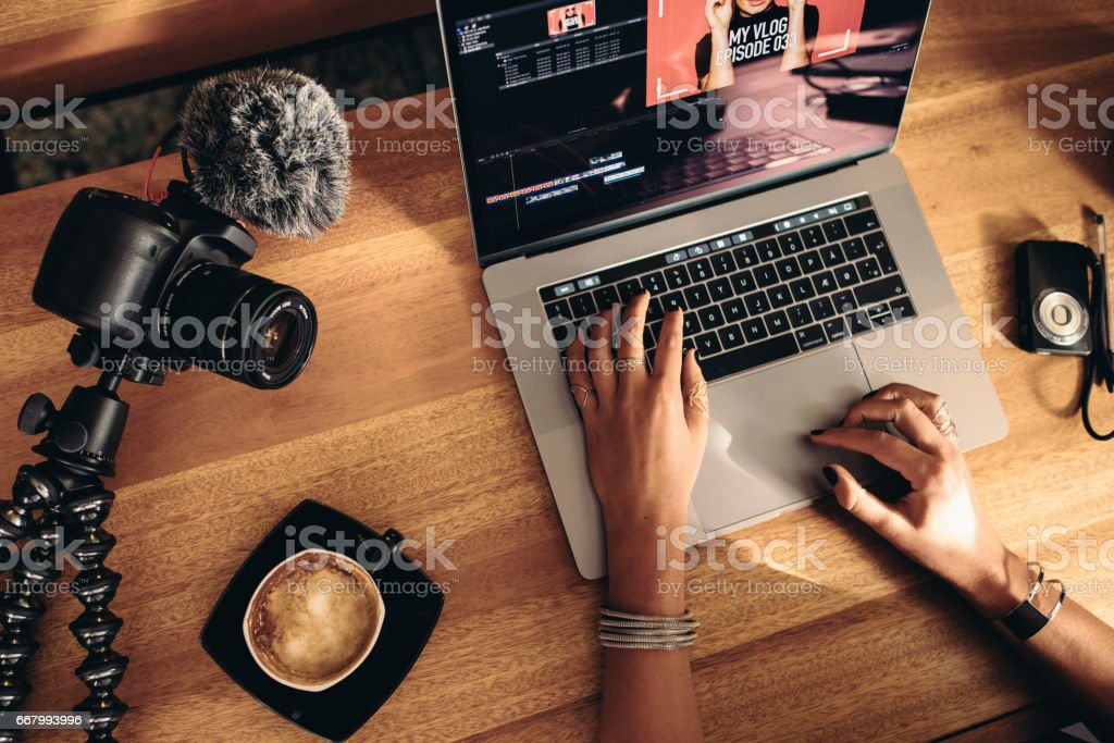 Young female vlogger editing her vlog on computer. stock photo