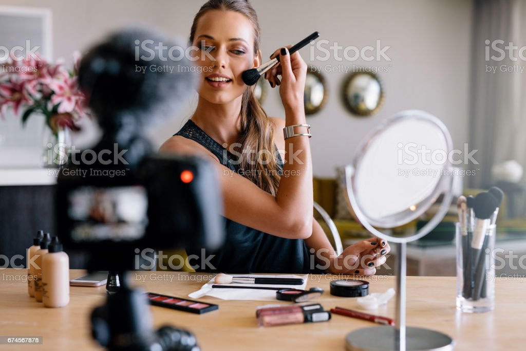 Young female vlogger recording a make-up broadcast. stock photo