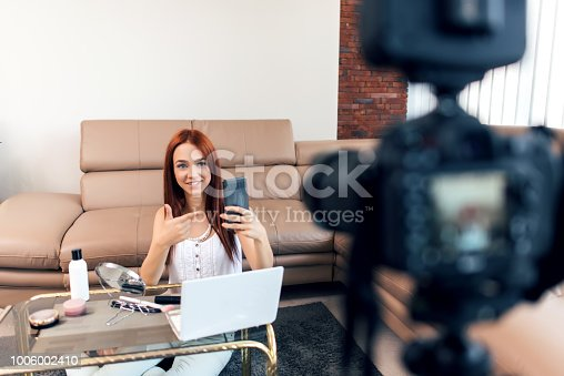 istock Young female vlogger recording a make-up video for her vlog. 1006002410
