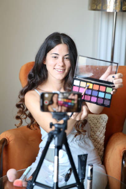 Young female vlogger recording a make-up video for her vlog stock photo