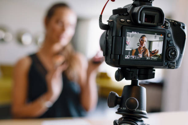 Young female vlogger recording a make-up video for her vlog. stock photo