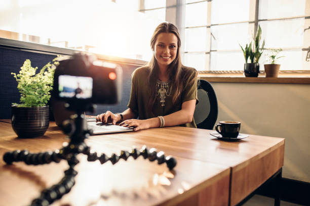 Young female vlogger recording content for her video blog. stock photo