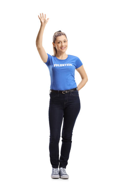 Young female volunteer waving at the camera Full length portrait of a young female volunteer waving at the camera isolated on white background contributor stock pictures, royalty-free photos & images