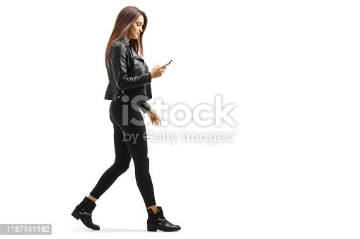 Full length profile shot of a young female walking and looking at her mobile phone isolated on white background
