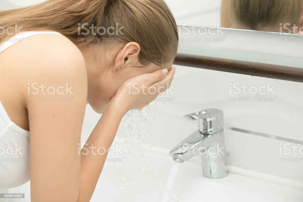 Young female washing her face tap clear water near sink - foto de acervo
