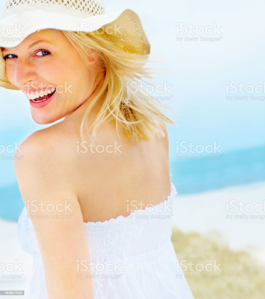 Young female wearing a beach hat and looking at you stock photo