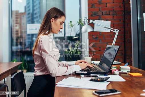 istock Young female wearing formal clothes working on laptop typing emails sitting at her workplace 876471020