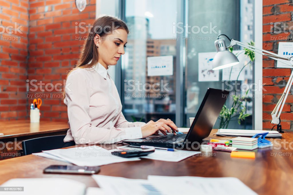 Young female wearing formal clothes working on laptop typing emails sitting at her workplace - Royalty-free 20-29 Years Stock Photo