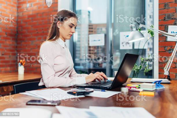 Young Female Wearing Formal Clothes Working On Laptop Typing Emails Sitting At Her Workplace Stock Photo - Download Image Now