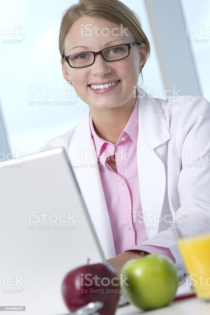 Young female wearing lab coat sitting at desk with laptop royalty-free stock photo