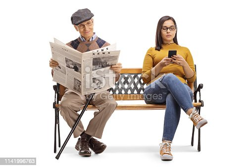 Full length portrait of a young female with a mobile phone and a senior man reading a newspaper on a bench isolated on white background