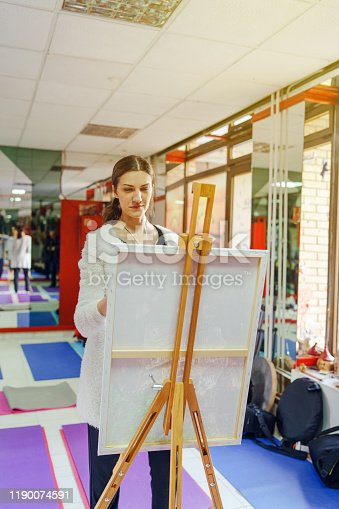 937313030 istock photo Young female woman girl painting on the canvas making art paint at home or studio 1190074591