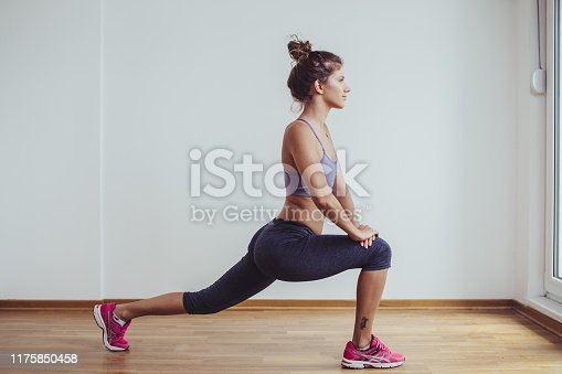 istock Young female woman workout at home 1175850458