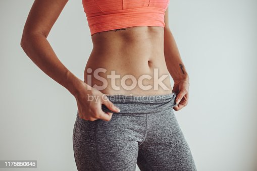 925799546 istock photo Young female woman workout at home 1175850645